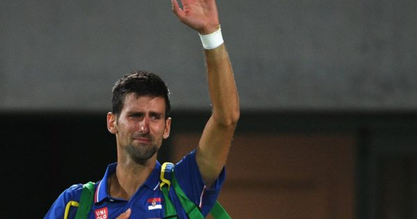 TOPSHOT - Serbia's Novak Djokovic waves to the crowd with tears in his eyes after losing his men's first round singles tennis match against Argentina's Juan Martin Del Potro at the Olympic Tennis Centre of the Rio 2016 Olympic Games in Rio de Janeiro on August 7, 2016. / AFP PHOTO / Roberto SCHMIDT